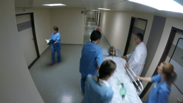 pov medical team pushing a young male patient on a stretcher - ward stock videos & royalty-free footage