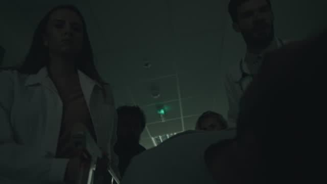 vídeos de stock e filmes b-roll de medical team pushing emergency stretcher - surgeon