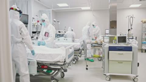 vídeos de stock e filmes b-roll de medical team rolling senior male patient into icu - equipamento respiratório