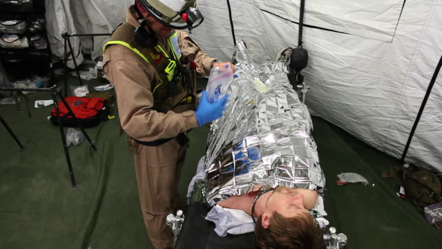 HANDHELD WIDE SHOT medical team talks to and moves injured people on stretchers in tent - members of US Marines and FDNY take part in joint drill aimed at strenghting preparedness for chemical and biological attacks at Barclays Center