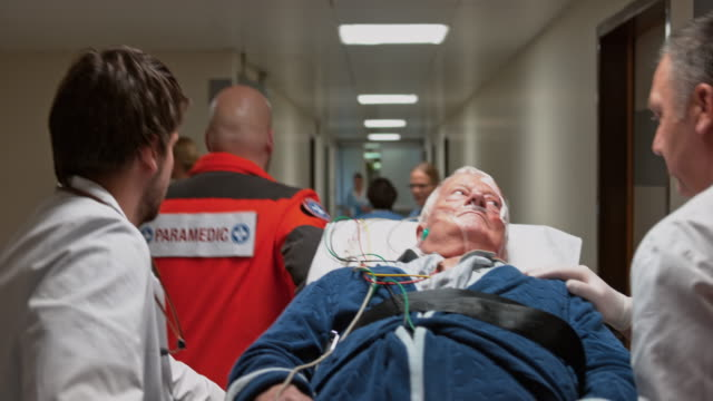 medical team transporting a male senior patient to the emergency room - krankenhaus rollbett stock-videos und b-roll-filmmaterial
