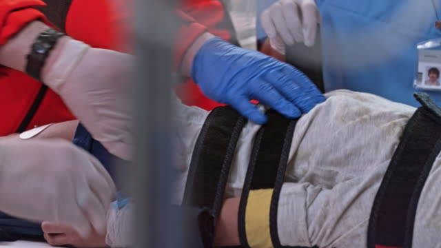 medical team unstrapping a child patient on a spinal board - emergencies and disasters stock videos & royalty-free footage