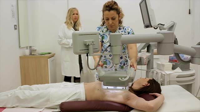 vídeos de stock, filmes e b-roll de técnica médica prepara o paciente para o exame das mamas no mais moderno aparelho de ultra-som - ultrassom 3d