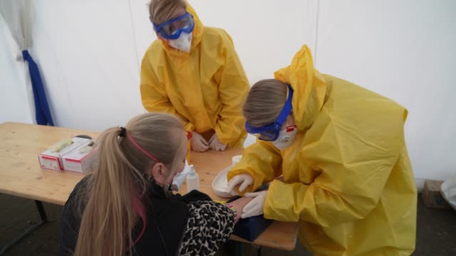 medical volunteers dressed in protective suits masks gloves and goggles take blood samples from visitors with symptoms to test them for covid19... - symptom stock videos & royalty-free footage