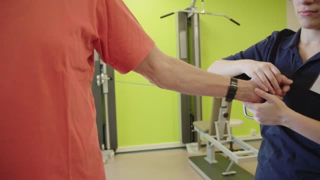 vídeos y material grabado en eventos de stock de trabajador médico que ayuda a los ancianos en el ejercicio - fisioterapia deportiva