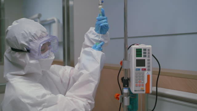 a medical worker checking a patient in protective clothing to prevent covid-19 at hospital - iv drip stock videos & royalty-free footage