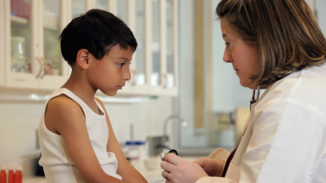 'medical worker checking the heart of a hispanic child patient/Richmond,Virginia, USA'