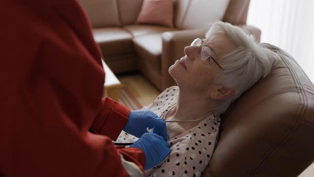 operatore medico che esamina il paziente anziano durante la chiamata a casa - apparato respiratorio video stock e b–roll