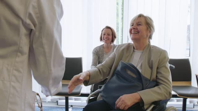 vidéos et rushes de travailleur médical serrant la main avec la famille dans le hall - hall d'entrée
