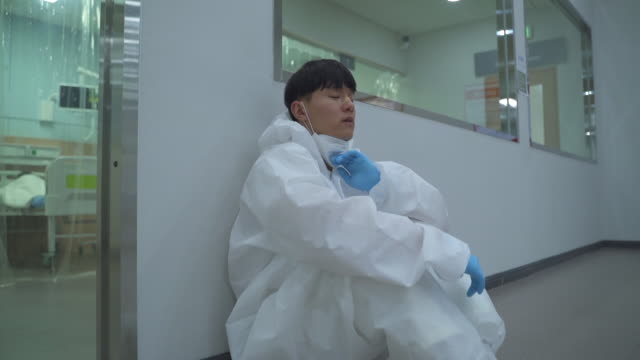 a medical worker sitting and smiling with thumbs up sign in protective clothing while taking off protective masks to prevent covid-19 - korean ethnicity stock videos & royalty-free footage