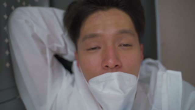 a medical worker smiling while taking off a protective mask to prevent covid-19 - 取り除く点の映像素材/bロール