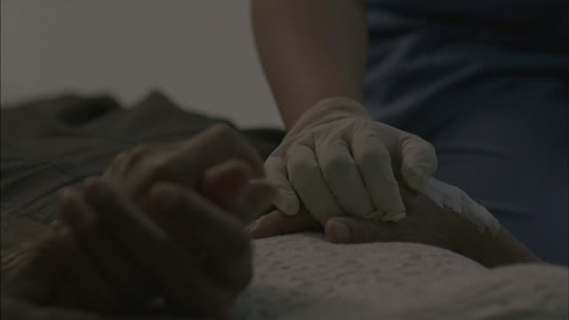 a medical worker with surgical gloves holds a patient's hand. - holding hands stock videos & royalty-free footage