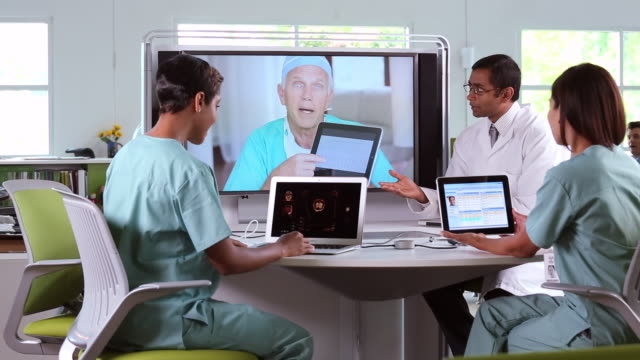 MS Medical Workers Discussing Patient Information with Doctors Using Video Conference / Richmond, Virginia, USA