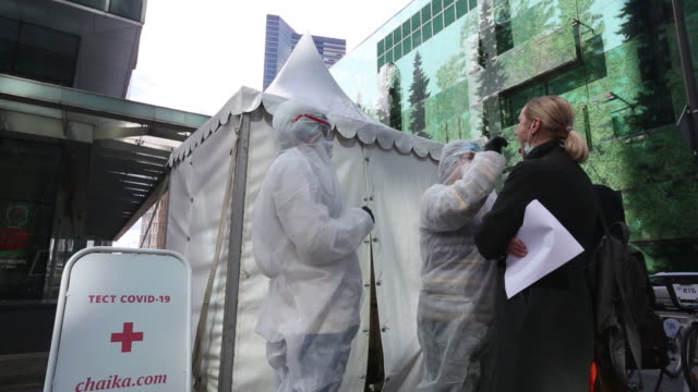 medical workers dressed in personal protective equipment prepare to take a swab sample from a visitor at a chaika clinic mobile covid-19... - russia点の映像素材/bロール