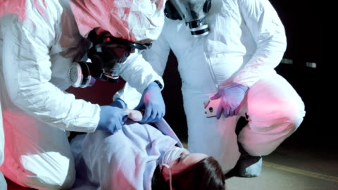 stockvideo's en b-roll-footage met medical workers helping ebola patient - epidemie