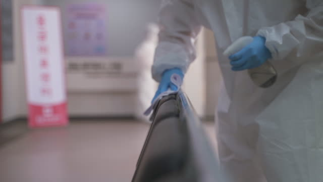 vidéos et rushes de medical workers in protective clothing sanitizing and disinfecting the hospital building to prevent covid-19 - nettoyer