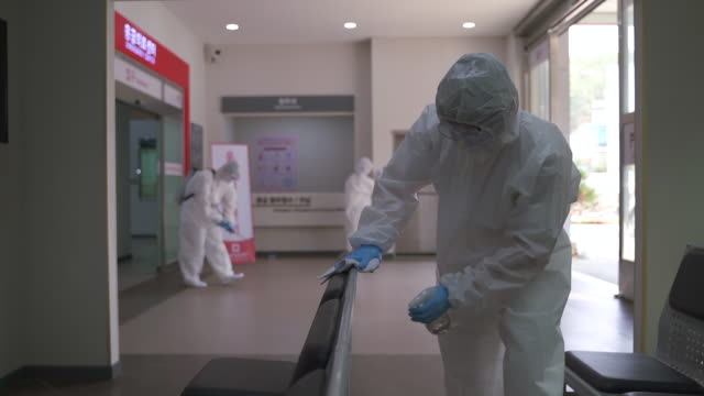medical workers in protective clothing sanitizing and disinfecting the hospital building to prevent covid-19 - protective workwear stock videos & royalty-free footage