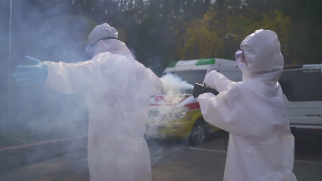medical workers in protective clothing sanitizing and disinfecting the hospital building to prevent covid-19 - クリーンスーツ点の映像素材/bロール