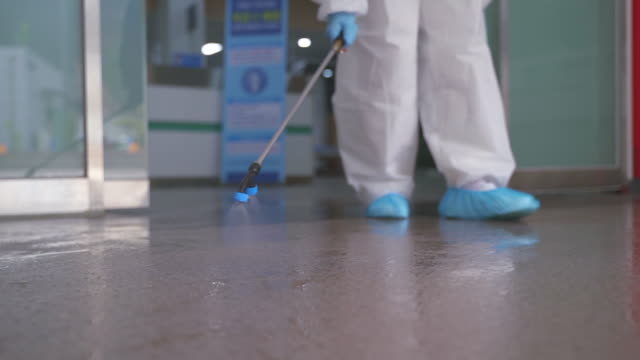 medical workers in protective clothing sanitizing and disinfecting the hospital building to prevent covid-19 - 東アジア点の映像素材/bロール
