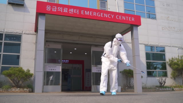 vidéos et rushes de medical workers in protective clothing sanitizing and disinfecting the hospital building to prevent covid-19 - tous types de crises