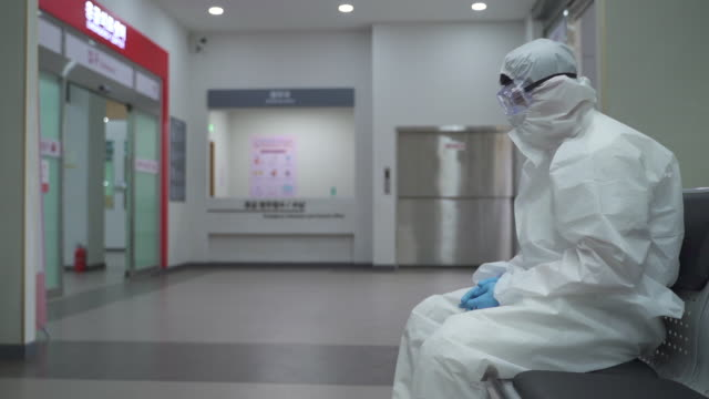 medical workers in protective clothing to prevent covid-19 running for patient transport while a tired one getting rest - exhaustion stock videos & royalty-free footage