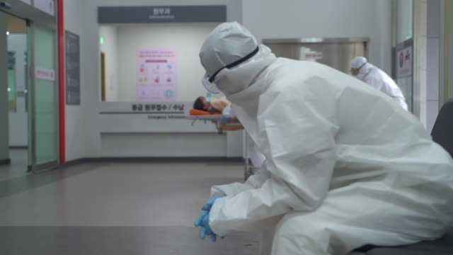 medical workers in protective clothing to prevent covid-19 running for patient transport while a tired one getting rest - krankenhaus rollbett stock-videos und b-roll-filmmaterial
