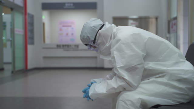vidéos et rushes de medical workers in protective clothing to prevent covid-19 running for patient transport while a tired one getting rest - pandémie