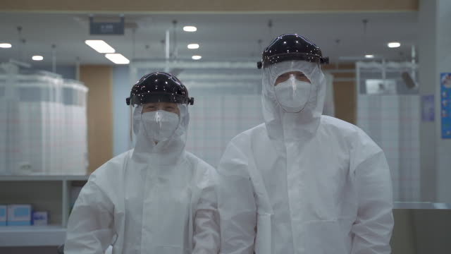medical workers making fist pump in protective clothing to prevent covid-19 at hospital - korean ethnicity stock videos & royalty-free footage
