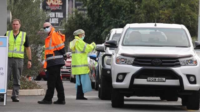 stockvideo's en b-roll-footage met medical workers prepare tests for people in vehicles waiting in a queue at an outdoor pop-up covid-19 testing site clinic on july 11, 2020 in the... - sydney australië