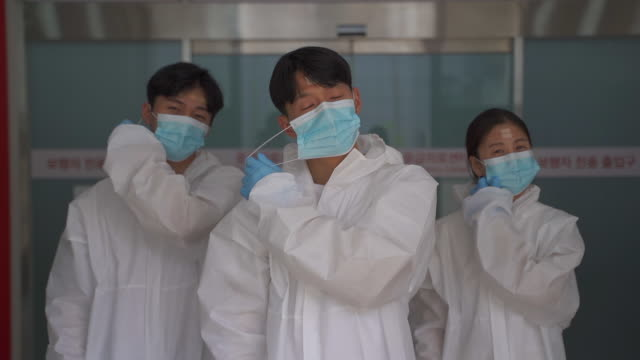 medical workers smiling in protective clothing while taking off protective masks to prevent covid-19 - absence stock videos & royalty-free footage