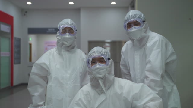 stockvideo's en b-roll-footage met medical workers smiling with thumbs up sign in protective clothing to prevent covid-19 - protective workwear