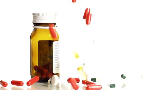 hd slow motion: medicaments falling over pill bottle - prescription medicine bottles stock videos & royalty-free footage