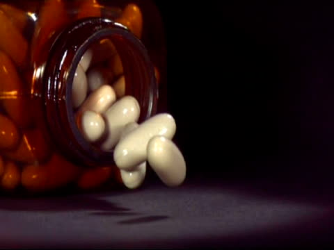 slo mo - cu medicine bottle falling, white capsules spill out - painkiller stock videos & royalty-free footage