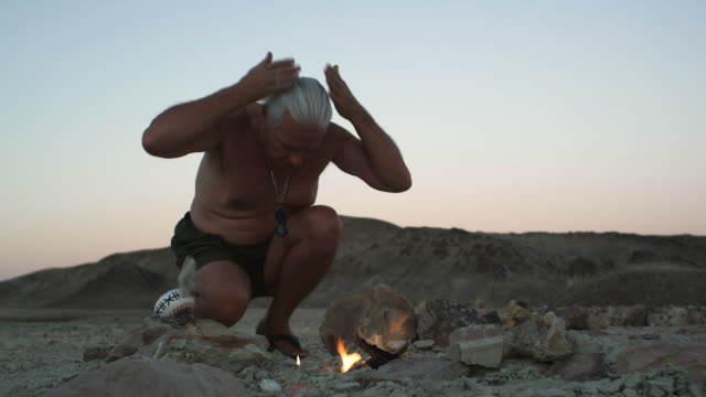 LA MS Medicine man igniting ceremonial fire at dusk / Tecopa, California, USA