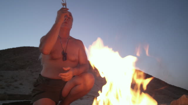 LA MS Medicine man praying over ceremonial fire at dawn / Tecopa, California, USA