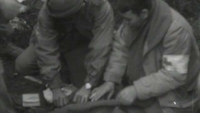 stockvideo's en b-roll-footage met medics carrying an injured soldier on a stretcher cutting off the bandage and attending to his head wound / france - gewonde