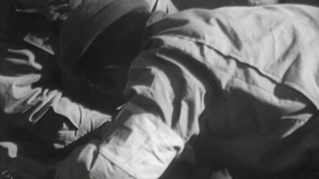 stockvideo's en b-roll-footage met medics filling out paperwork as casualty arrives examining casualty cutting bloody bandage from soldier's arm and treating injured arm / france - triage