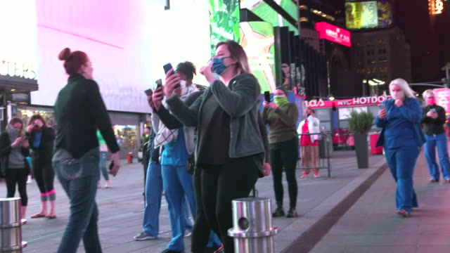 vídeos de stock, filmes e b-roll de medics from across the usa arrive in times square, new york city, to help hospitals with the coronavirus crisis, taking photos and applauding - aplanar a curva