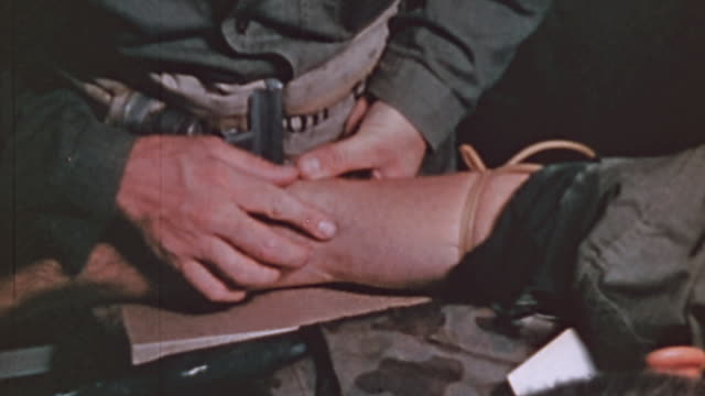 CU Medics inserting a needle into an injured soldier's arm and giving blood plasma to the soldier in the wardroom of USS Lubbock during World War II...
