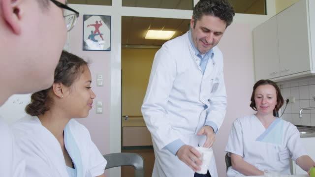 sanitäter nehmen arbeitspause im krankenhaus ein - chirurg stock-videos und b-roll-filmmaterial