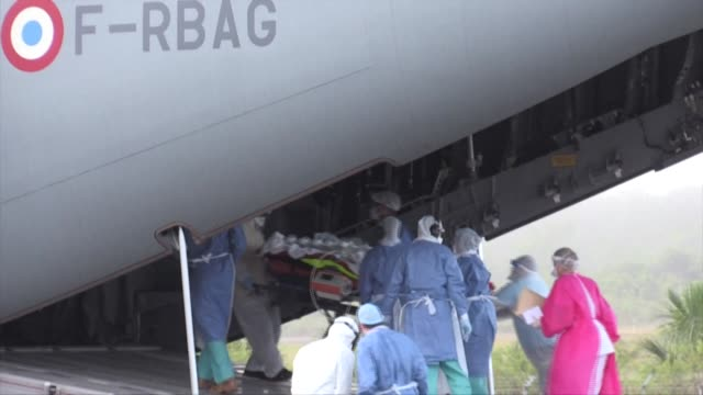 vídeos de stock, filmes e b-roll de medics wheel covid19 patients onto a a400m a military aircraft dedicated to transporting patients at cayenne airport in french guiana - territórios ultramarinos franceses