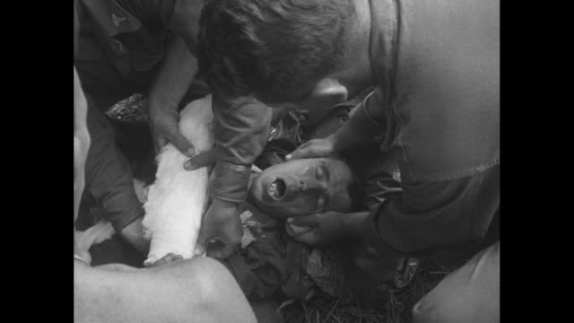CU medics work on soldier as he lies on ground / CU medic wraps bandage around soldier as he grimaces and screams / LS medics begin to lift soldier...