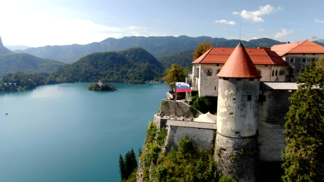vidéos et rushes de medieval bled castle with lake bled with slovenia flag blowing in wind - slovénie
