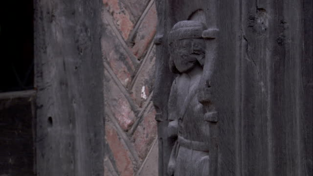 a medieval cottage features a carving inset into a wooden beam. available in hd. - lavenham stock-videos und b-roll-filmmaterial