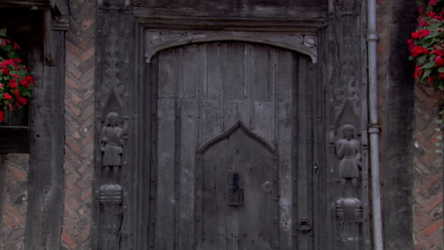 a medieval cottage features a wooden door flanked by carvings. available in hd. - lavenham stock-videos und b-roll-filmmaterial