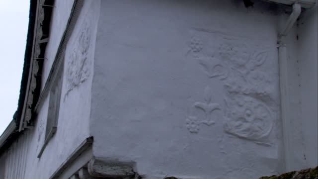 a medieval cottage features imprinted patterns on its exterior walls. available in hd. - lavenham stock-videos und b-roll-filmmaterial