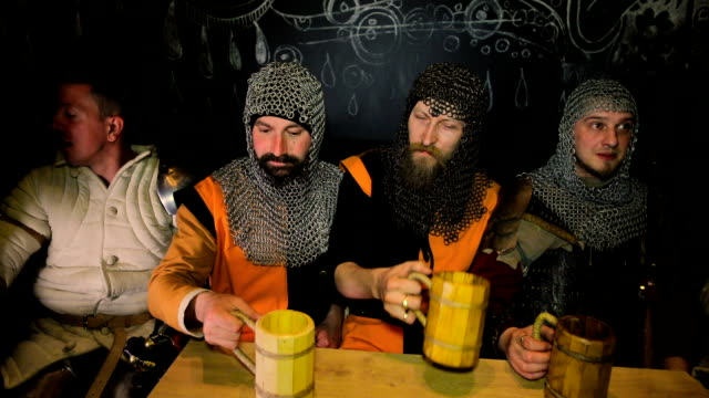 medieval knights drink beer on dark background - periodo medievale video stock e b–roll