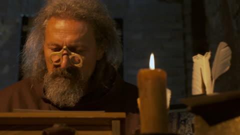 vídeos y material grabado en eventos de stock de dolly hd: medieval filósofo leer un libro - cristianismo