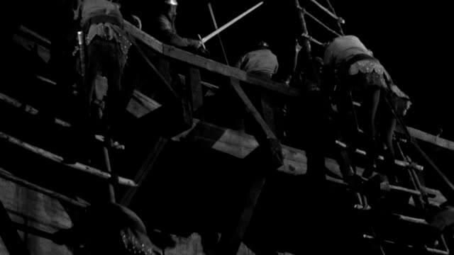 medieval soldiers fight with swords, while some of them back down rope ladders or fall. - battle stock videos & royalty-free footage