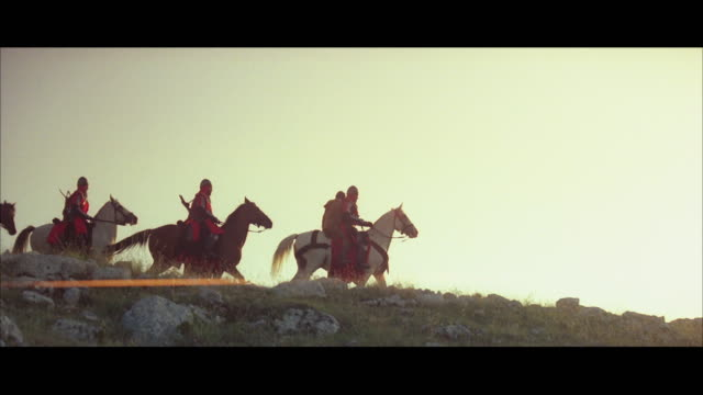 ws pan medieval soldiers riding horses across countryside - periodo medievale video stock e b–roll